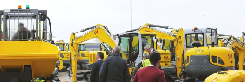 Some people looking at yellow construction diggers and dumpers at Wacker Neuson in Stafford