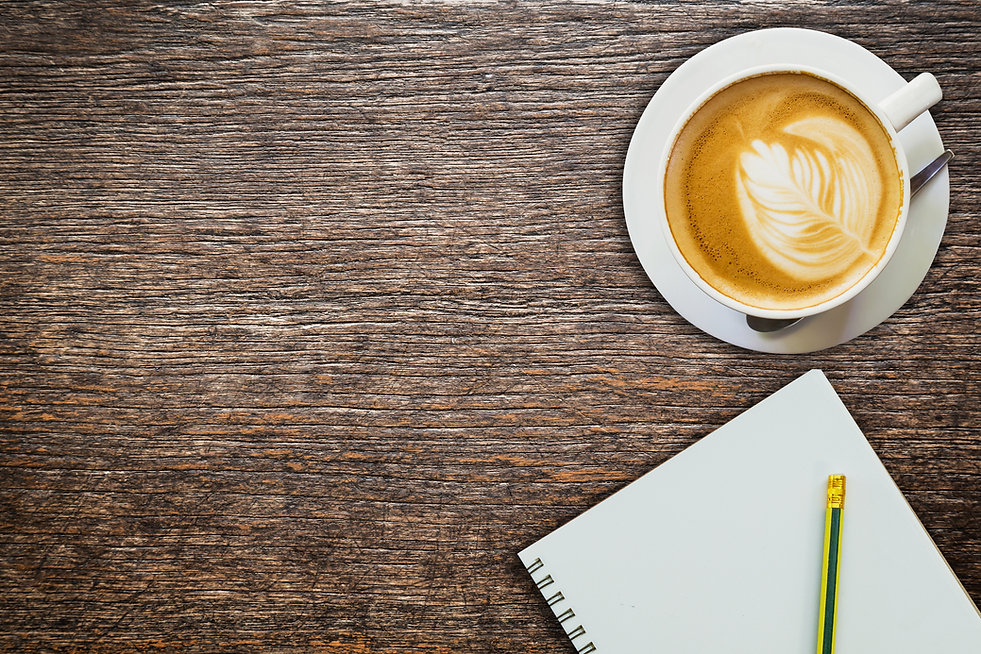 Table with coffee, notepad, and pencil