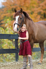 young equestrian in a dress posing with pony
