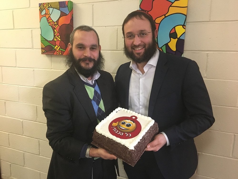 Rabbi Reavi Cooper accepts congratulatory cake fromRabbi Rabin at the RCV Special General Meeting