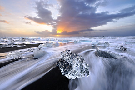Large ice chunks washed ashore on a beach in Iceland at sunrise.