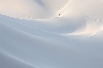 Local man walks in the white sand dunes near the coast of Socotra island, Yemen