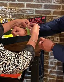 This greater has taken the guests temperature and is assisting them with their chosen wrist band signifying their comfort level with physical distancing.