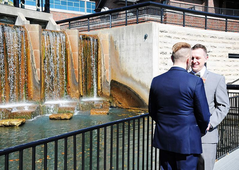 Real CANAL 337 couple James and Kevin in front of the stunning Fountain on the Indianapolis Canal with CANAL 337, A Thomas Venue in the background.