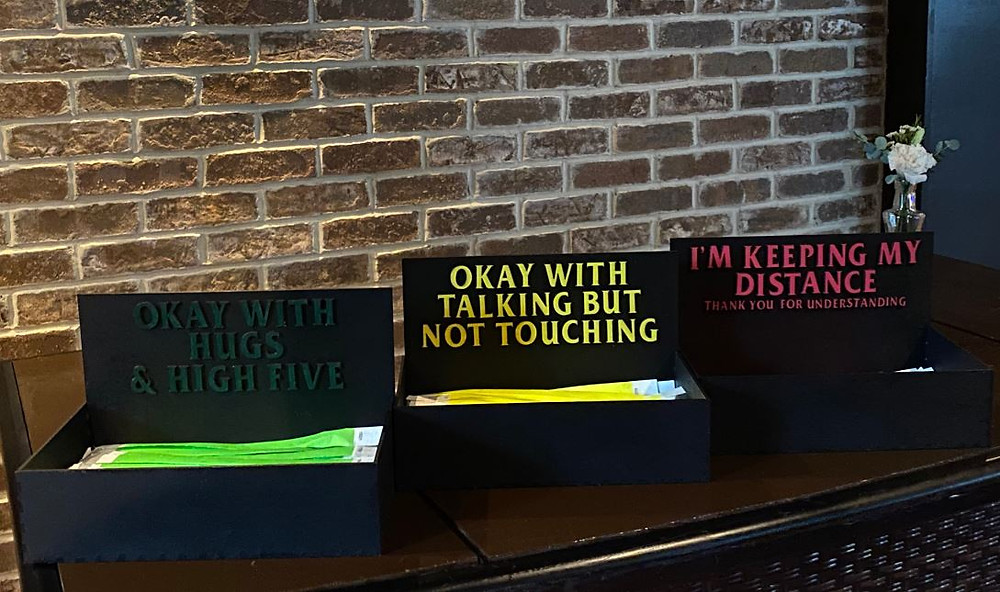 """A Green wrist band means they are comfortable with """"high-fives and handshakes"""". The yellow wrist bands are for the more cautious guests. Red wrist bands signify """"I am celebrating at a distance""""."""