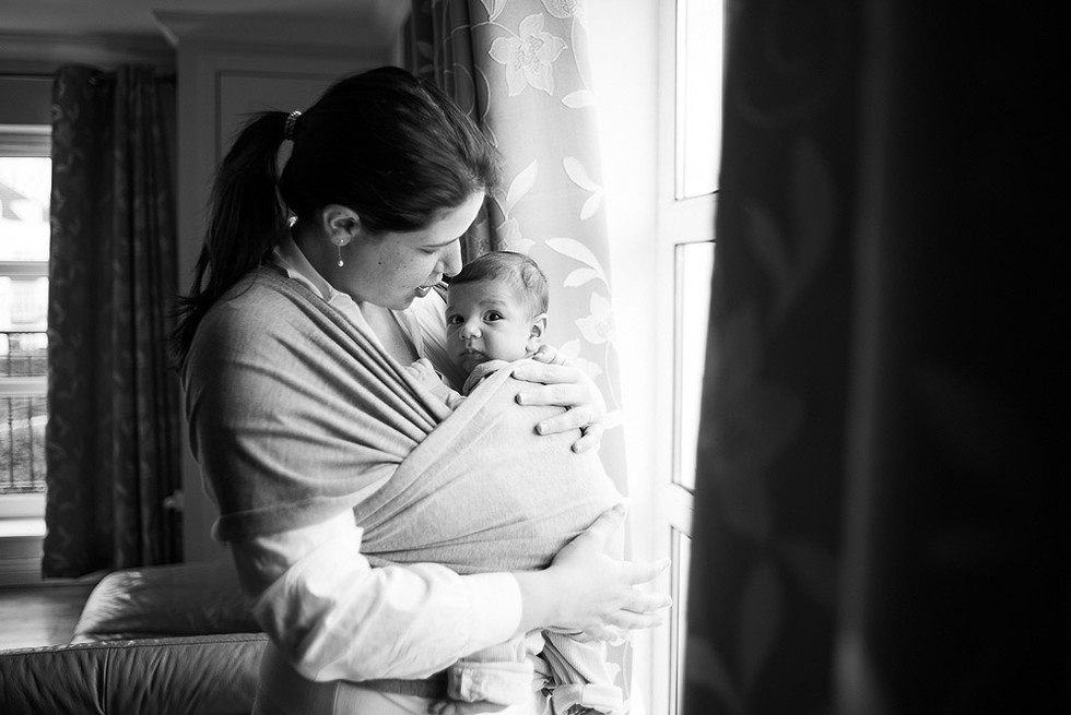 Mom with baby in a sling by the window