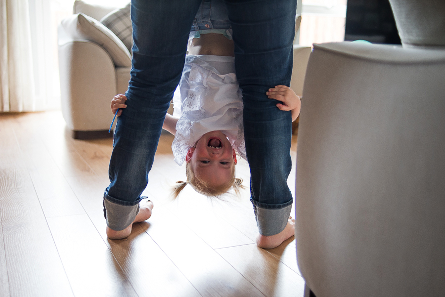 Little girl hanging upside down on mum's legs - Family Photography Session at home in Dublin by Camila Lee Family Photographer