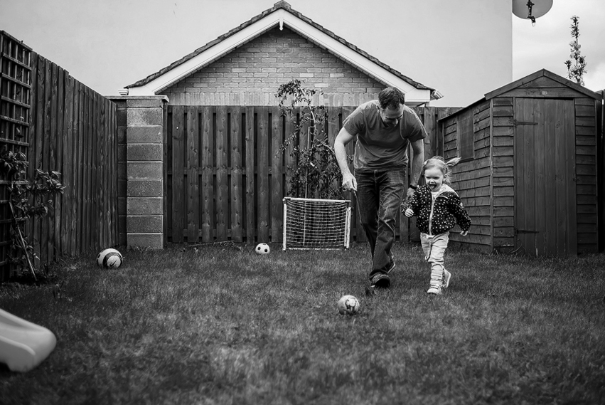 Dad and daughter playing football - Family Photography Session at home in Dublin by Camila Lee Family Photographer