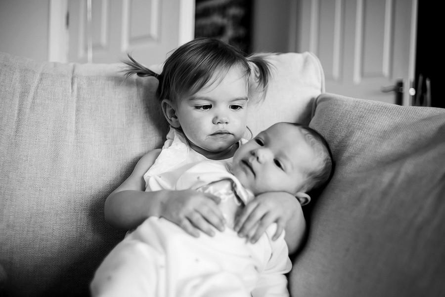 Big sister holding little baby girl