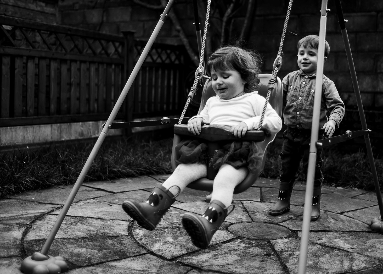 Kids playing in the swing in the back garden