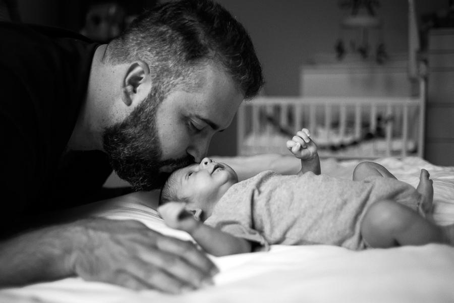 Dad kissing newborn baby. Photo by Camila Lee