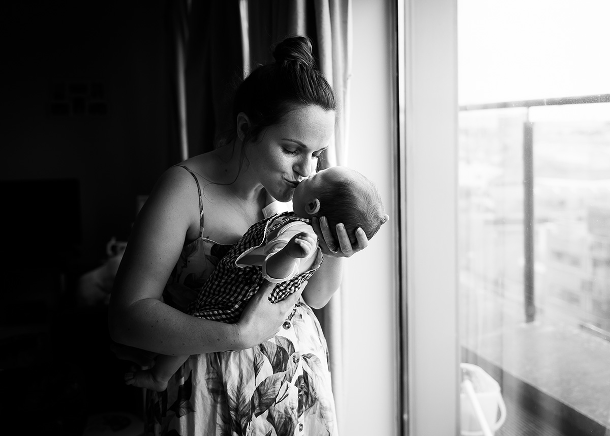 Mother kissing newborn baby by photographer Camilla Lee