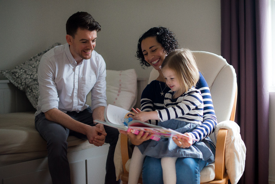 Mother and father reading for daughter