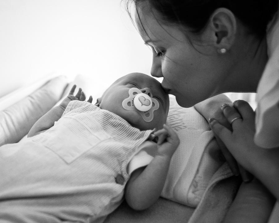 Mom kissing newborn baby. Photo by Camila Lee