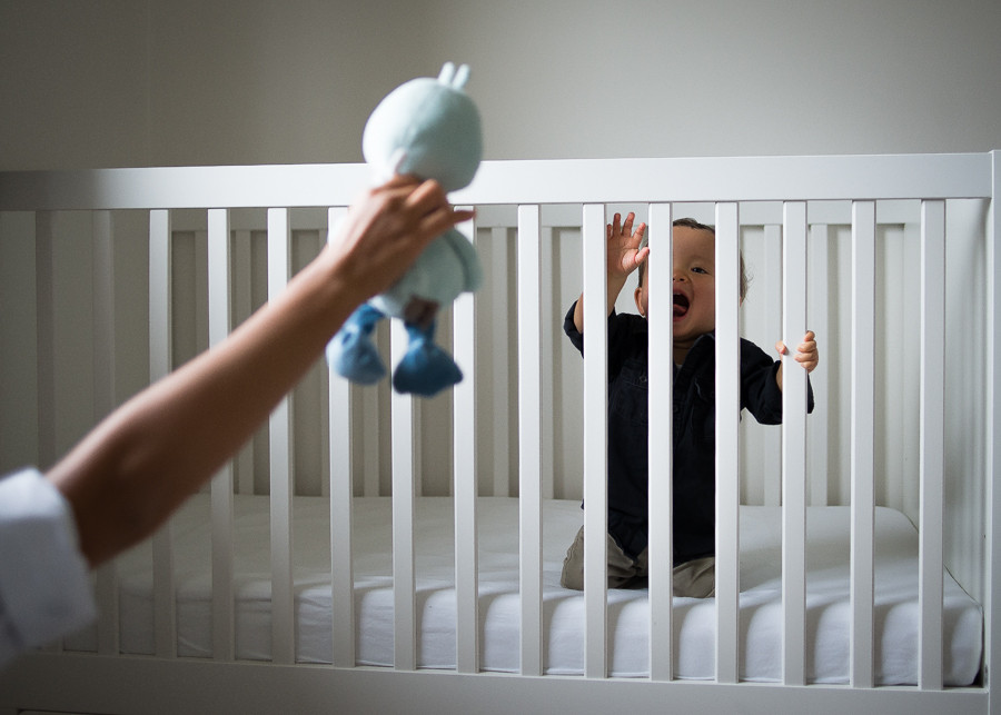 Smiley baby boy in a crib and mother's hand showing him a stuffy toy