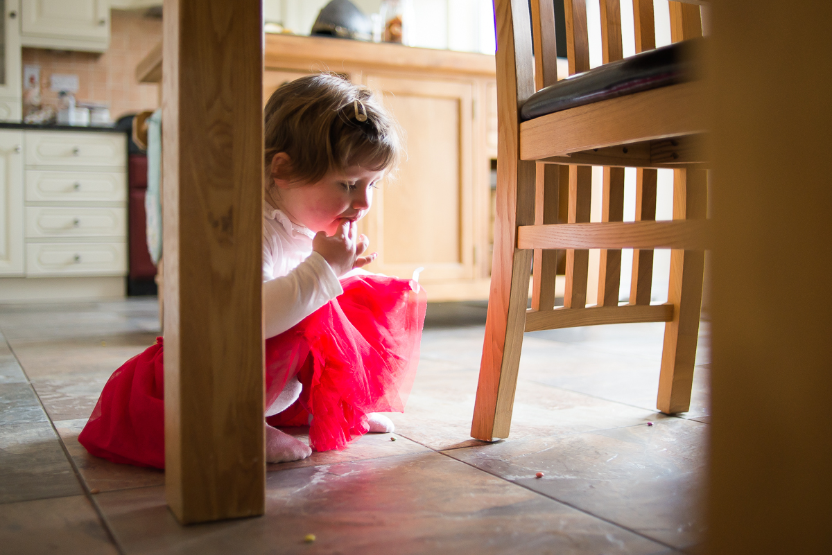 Little girl eating chocolate from the floor - Family photography session at home in Dublin by Camila Lee