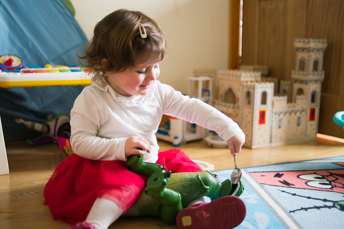 Little girl feeding her toy - Family photography session at home in Dublin by Camila Lee