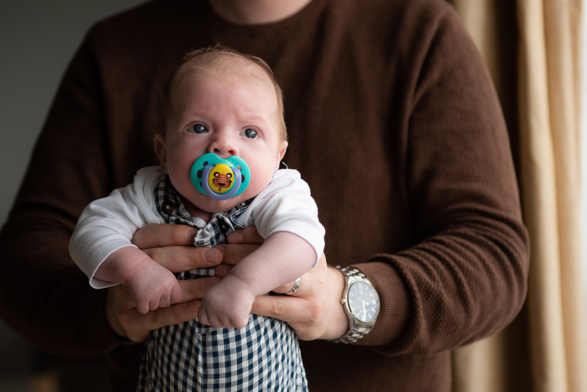 Dad holding newborn baby by Camilla Lee