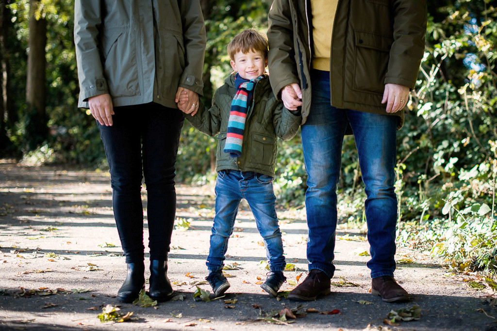 Little boy holding hands with parents at a park