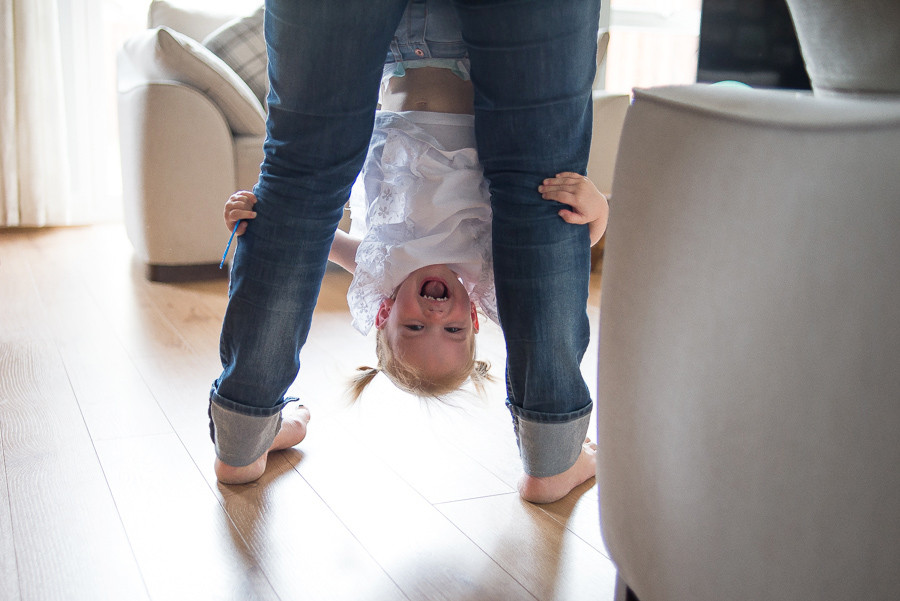 Girl hanging upside down on mothers legs