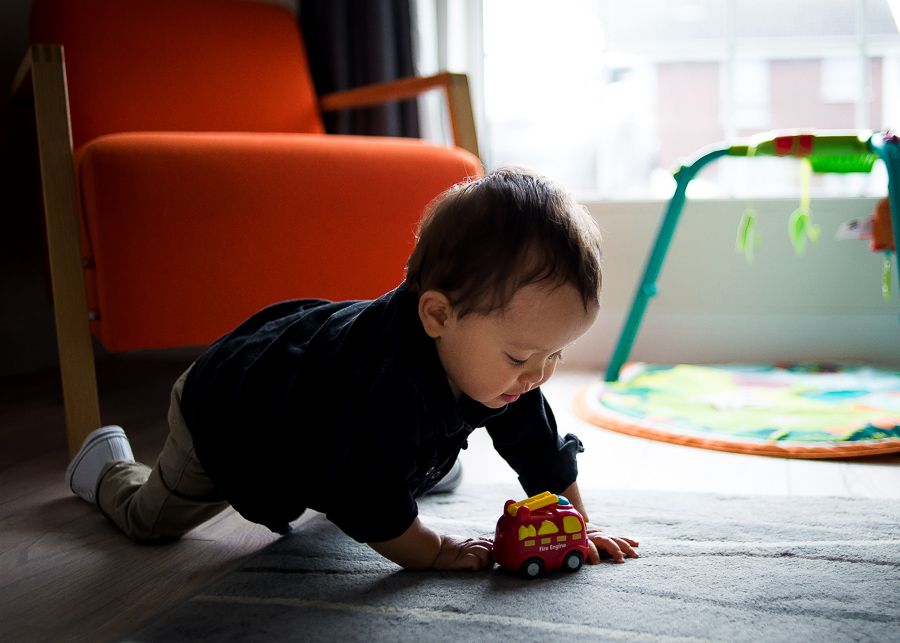 Baby boy playing with toy car - Family session at home in Dublin by Camila Lee