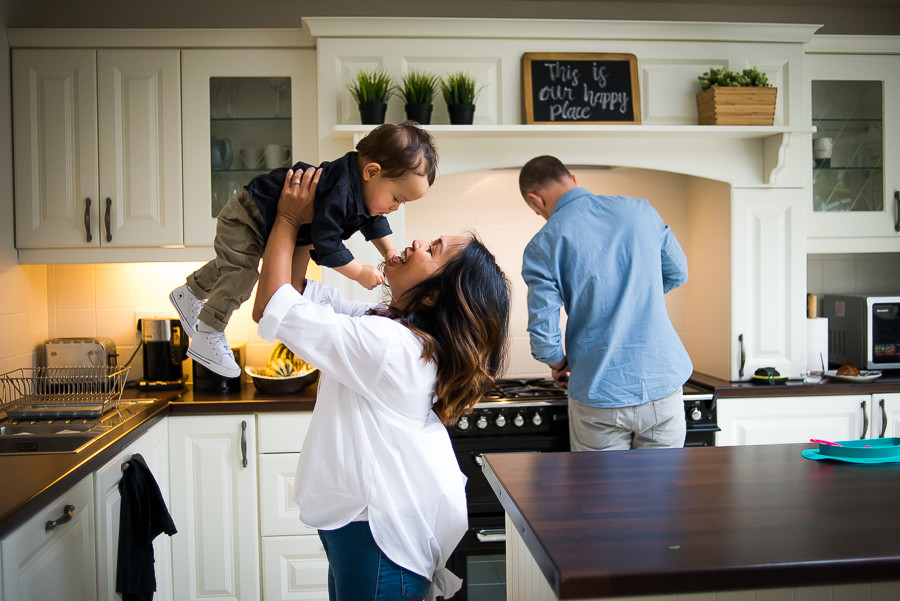 Mother holding baby boy up in the kitchen and father cooking
