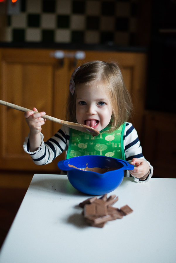 Little girl baking licking spoon - Family photoshoot at home in Dublin by Camila Lee
