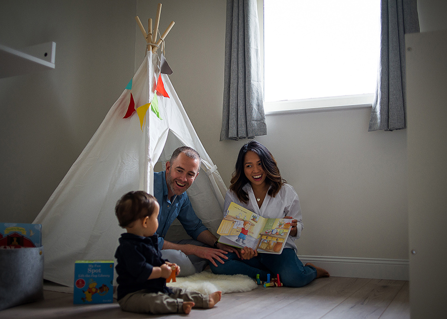 Mum and dad reading for baby boy - Family photography session at home in Dublin by Camila Lee