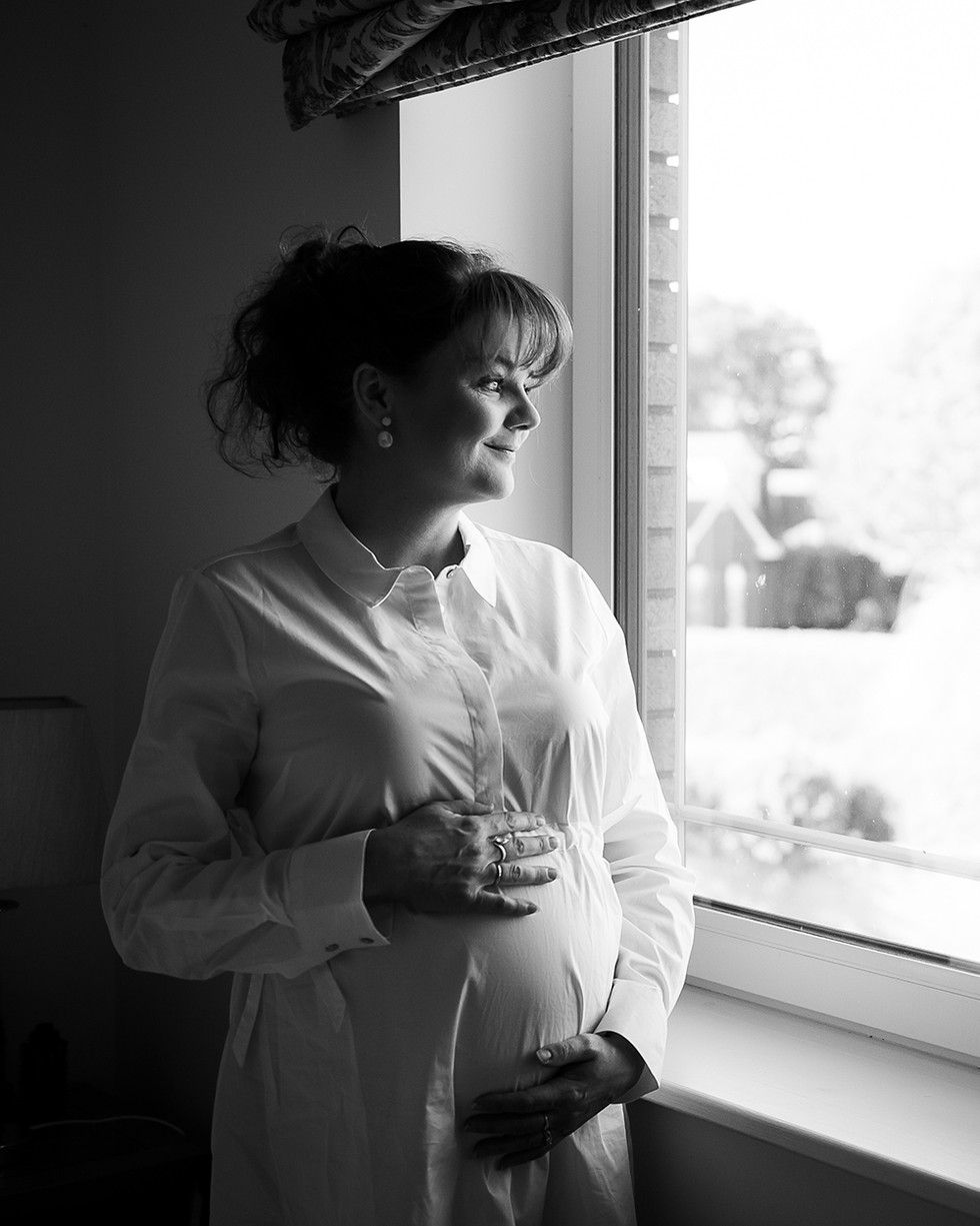 Pregnant woman looking out the window