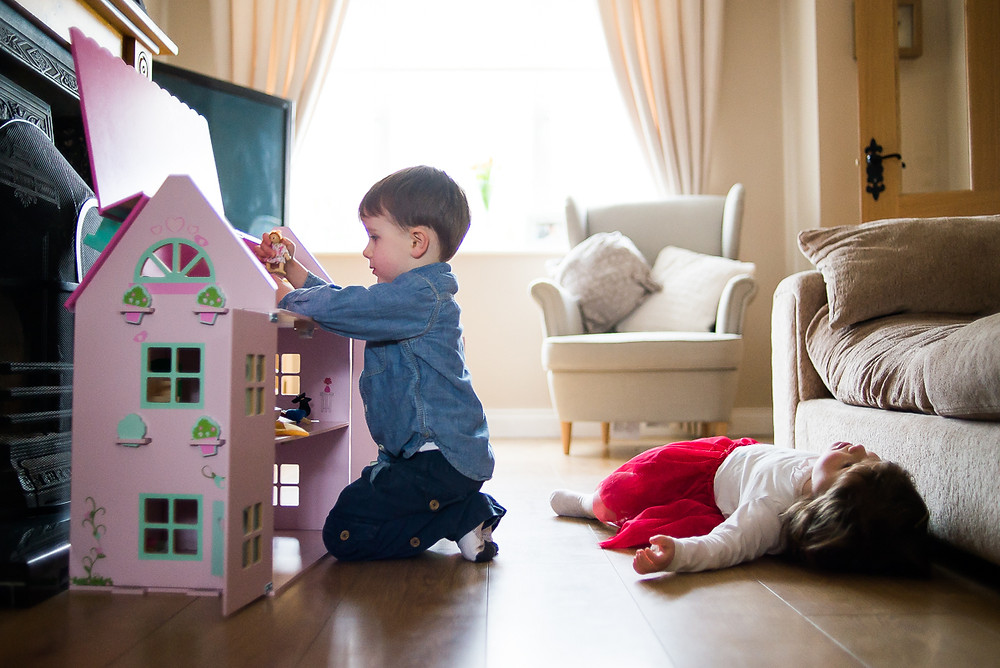 Little boy playing with sister's doll house - Family photography session at home in Dublin by Camila Lee