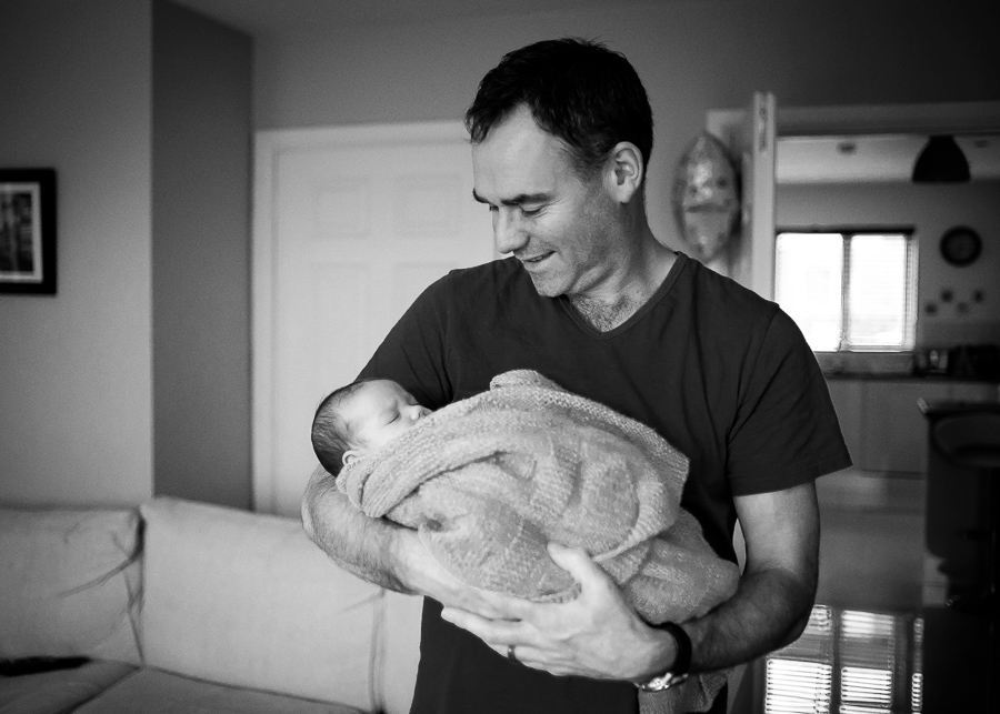 Father holding newborn baby. Photo by Camila Lee