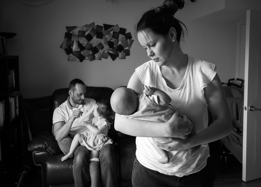 Mom holding newborn baby and dad with big sister