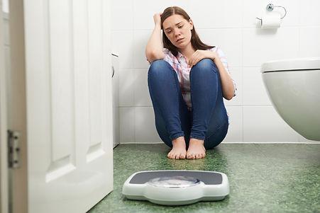 Unhappy Teenage Girl Sitting On Floor Looking At Bathroom Scales.jpg