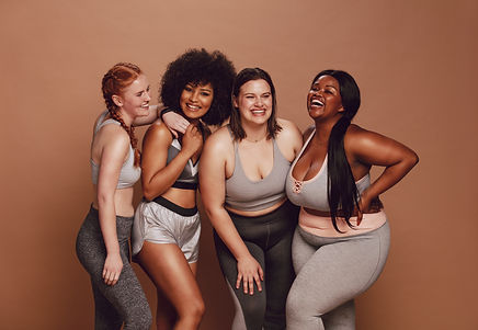 Smiling group of women in different size standing together in sportswear against brown bac