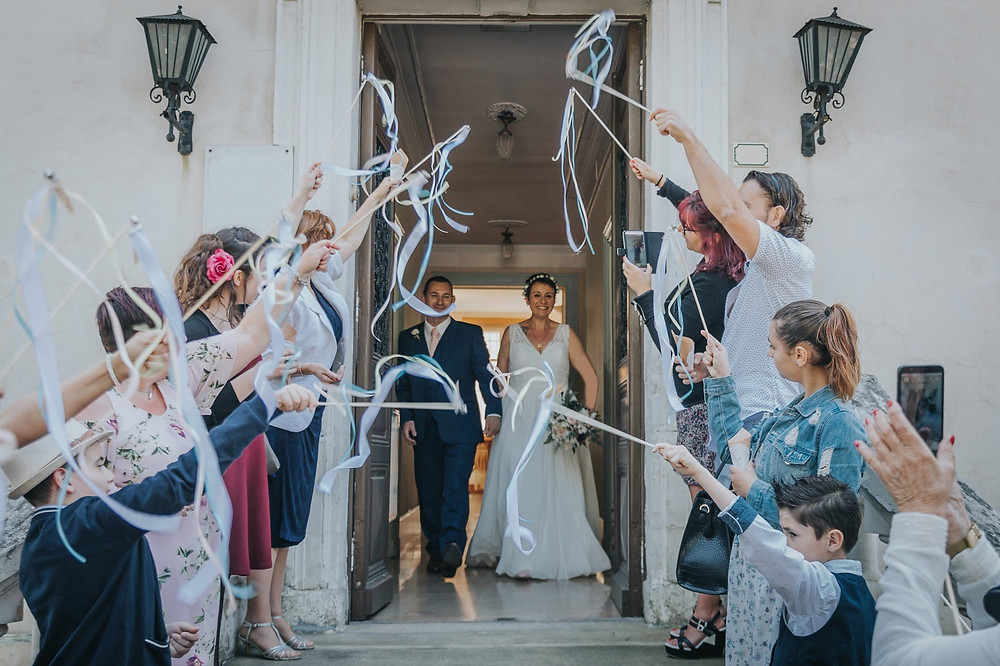 Sortie d'église des mariés avec des baguettes à rubans