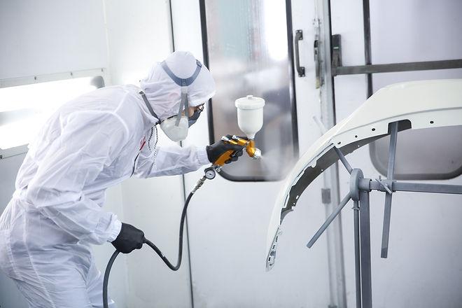 automobile repairman painter in protecti