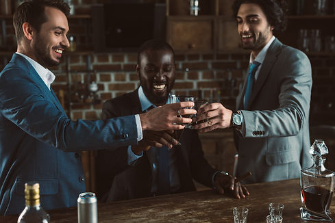 cheerful young male friends in suits clinking glasses of whiskey.jpg