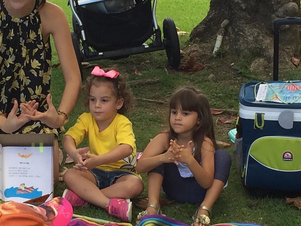 Las niñas llevando a cabo juegos con las manos al escuchar las rimas de Isabel Freire de Matos