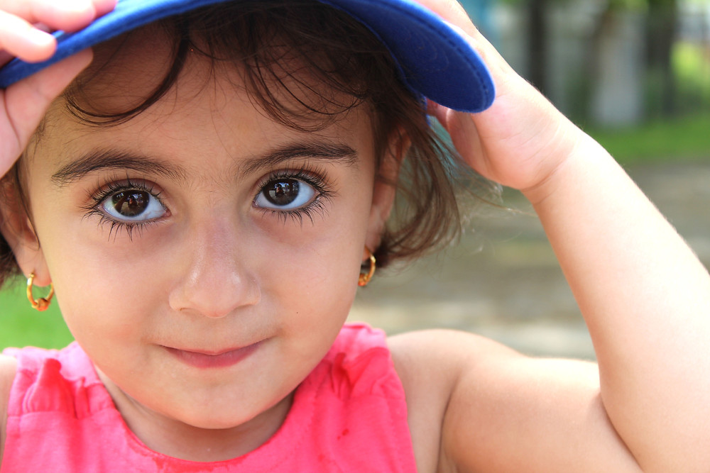 A young girl enjoys her new hat from the BBQ (Photo by: Kacie Cooper)