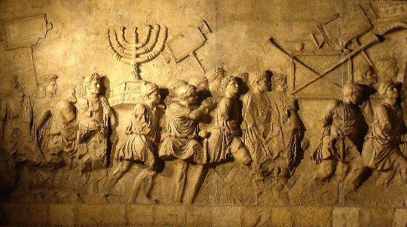 Panel from the Triumphal Arch of Titus in Rome, depicting a procession displaying objects taken from the Temple of Jerusalem after the sack of the city in AD 70.  By: Beth Hatefutsoth, CC BY 3.0 via Wikimedia Commons