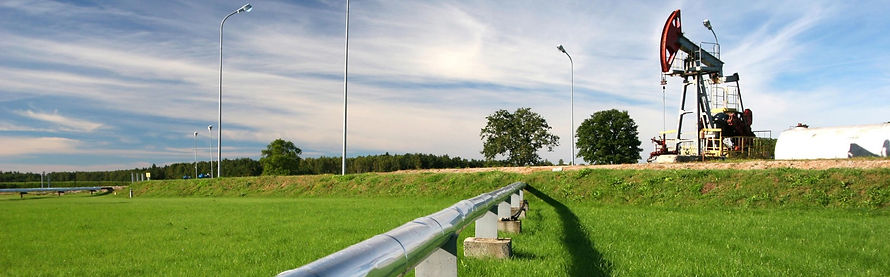 Above-ground pipeline and red pumpjack in a green field