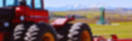 red farm tractor in a field with a green pumpjack and mountains
