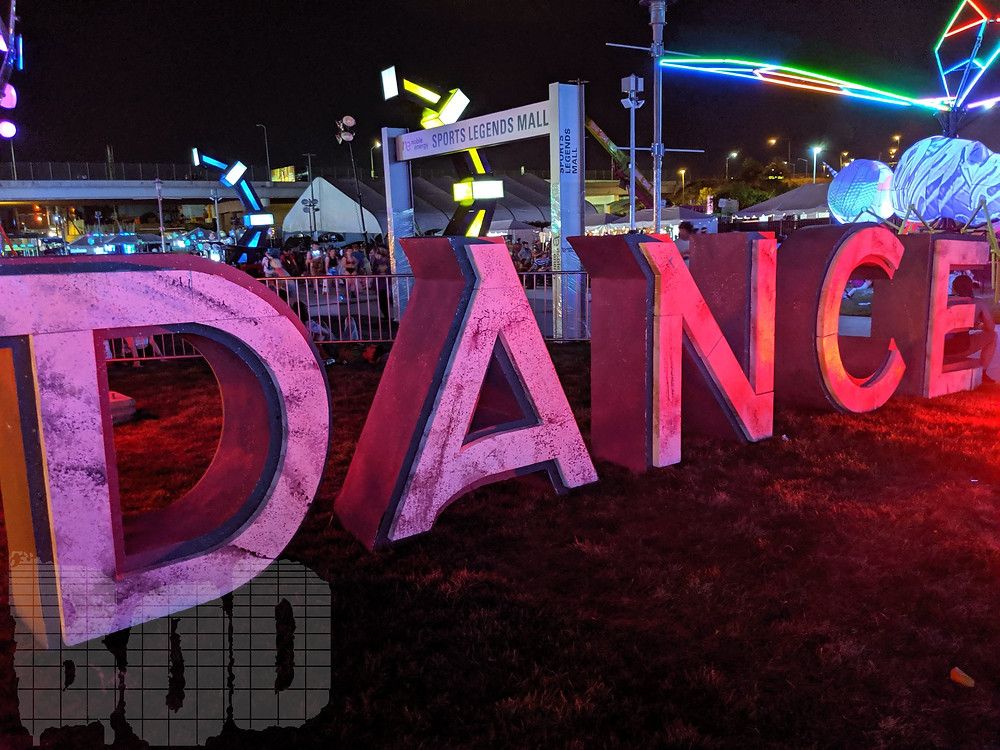 "Global Dance Festival glowing ""Dance"" signage at the event"