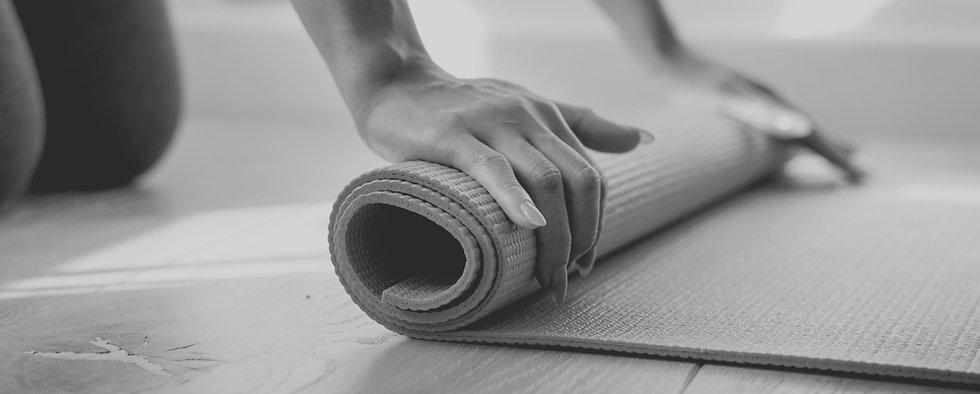woman-rolling-yoga-mat-2W6XGCN_edited.jp