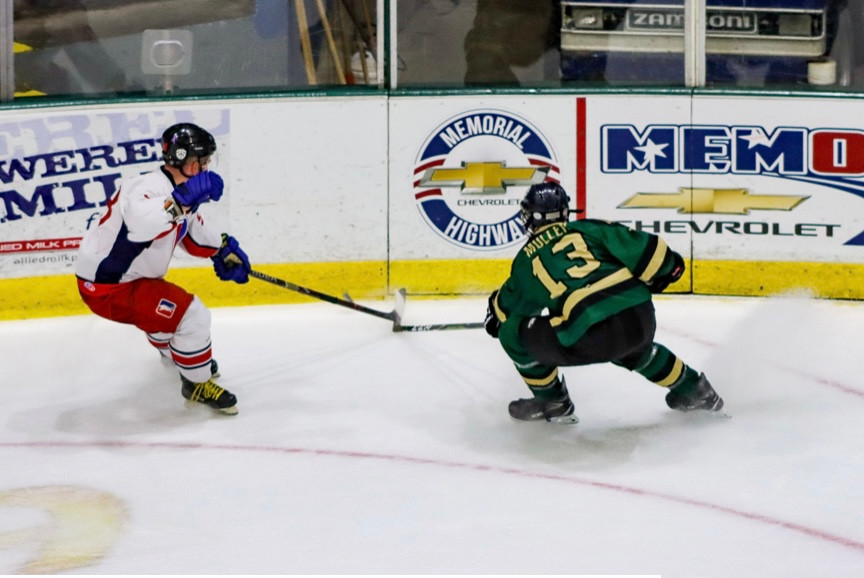 A Johnstown Generals player and Patriots Hockey player battle for a puck in the corner.