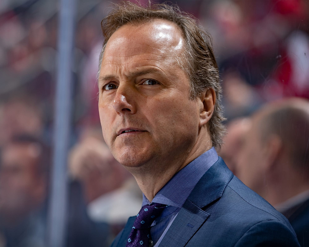 Jon Cooper standing behind the NHL's Tampa Bay Lightning during an NHL game.
