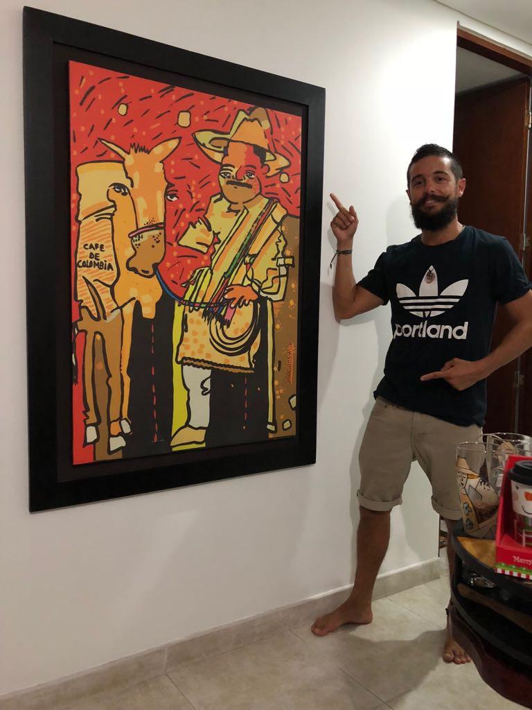 """Sergio feliz mostrando orgulloso su cuadro """"Juan Valdez y las malditas quiebrapatas"""""""