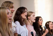 Group-of-women-singing-together-with-mic