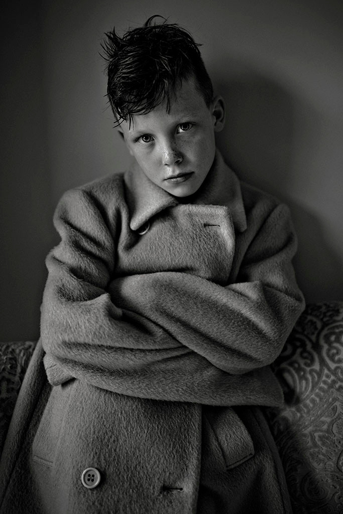 black & white portrait of boy in a coat