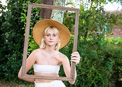 young woman in straw hat, holding picture frame